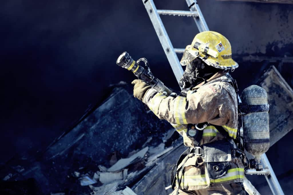Firefighter in full protective gear holding a fire nozzle