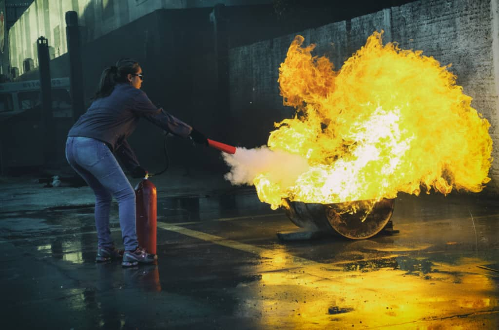 woman putting out fire with a fire extinguisher