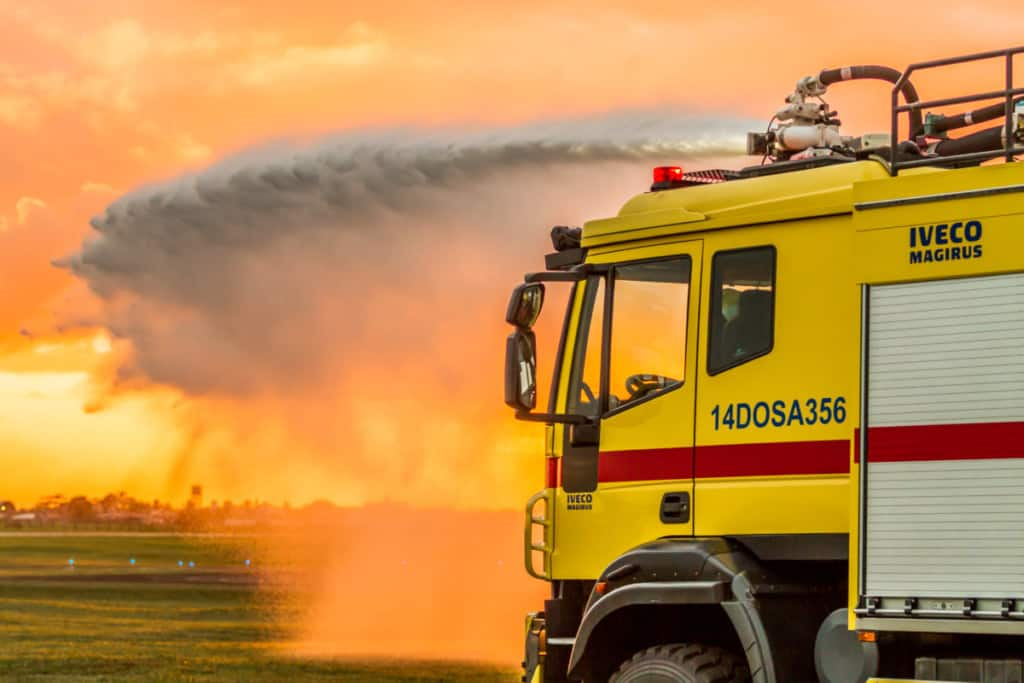 Airport fire apparatus spraying water from roof mounted nozzle