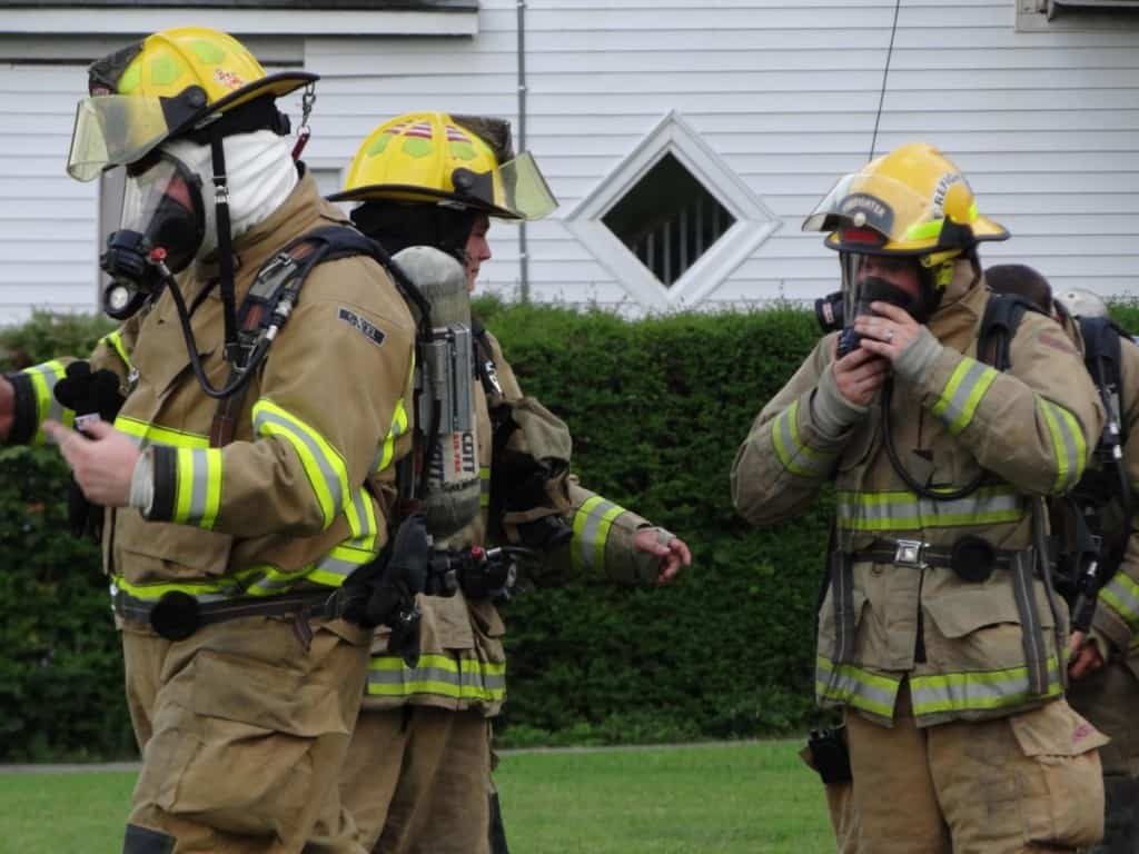 3 firefighters putting on protective gear