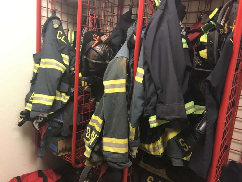 firefighter turnout coats and helmets hanging in lockers
