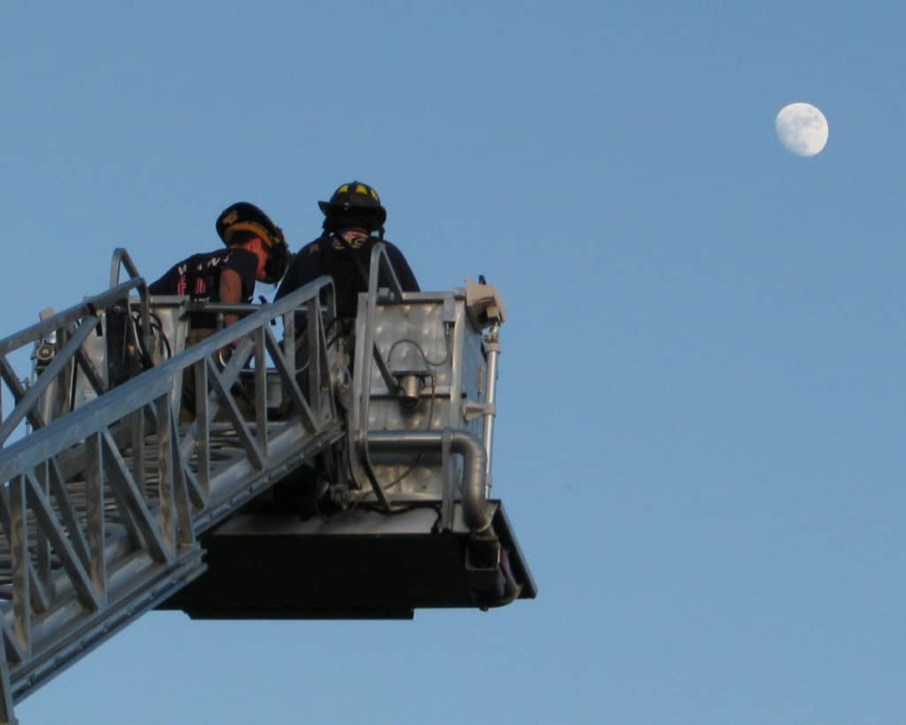 firefighters at the top of an aerial ladder, moon in background