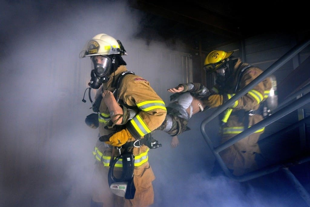 two firefighters carrying a dummy during a rescue drill