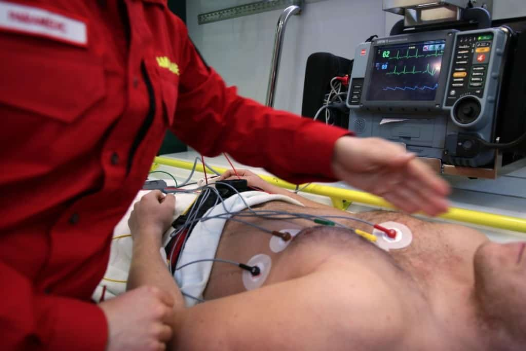 paramedic performing an EKG test on man lying down