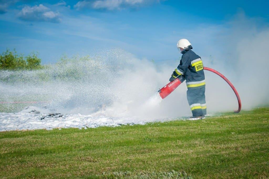 firefighter spraying foam onto grass