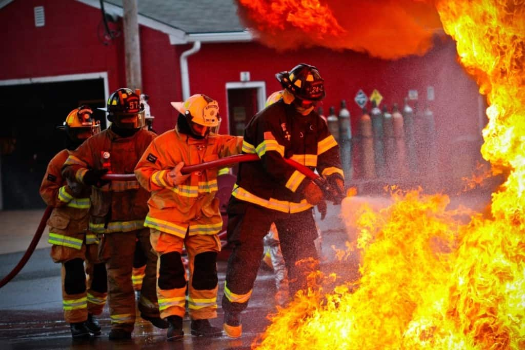 4 firefighters working to extinguish flames
