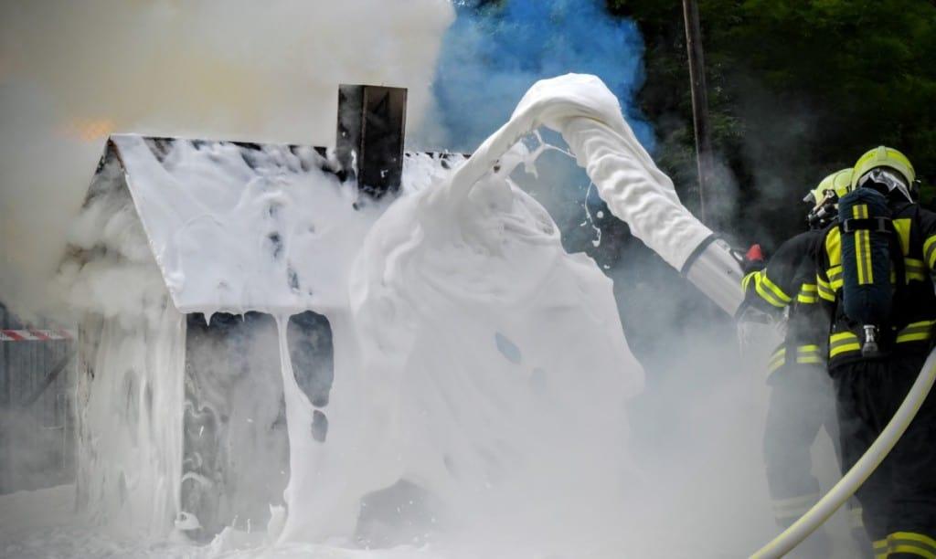 firefighters spraying foam onto house