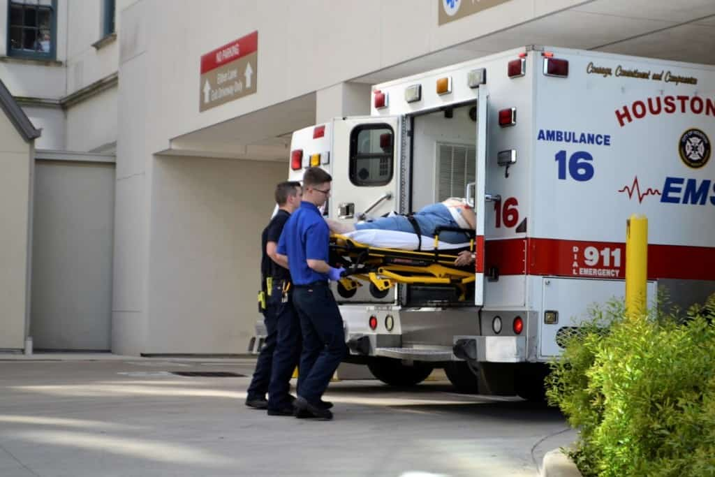 2 EMT's unloading patient on gurney from the ambulance