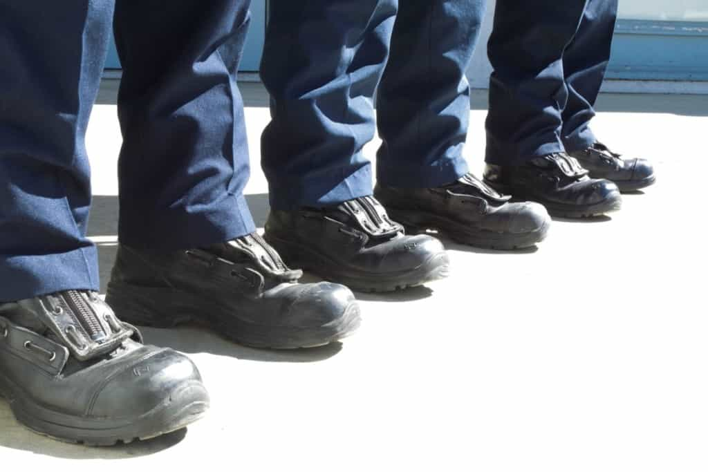 three pairs of firefighter station boots being worn