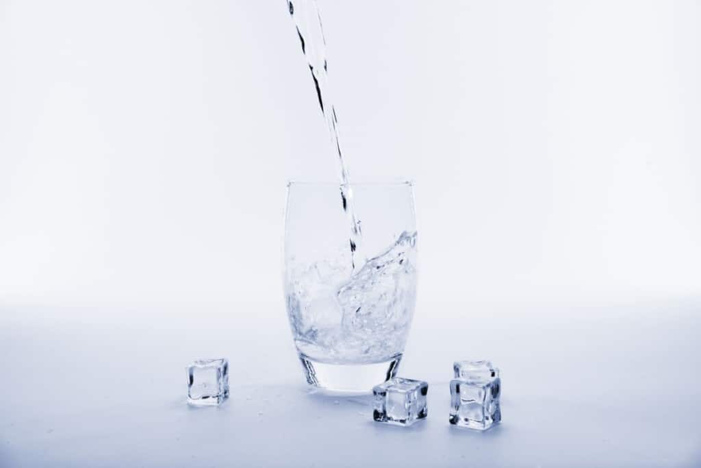 pouring cold water into glass with ice