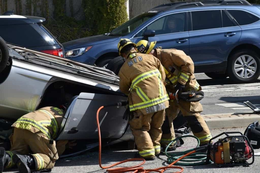 three firefighters working to remove a patient from a car accident