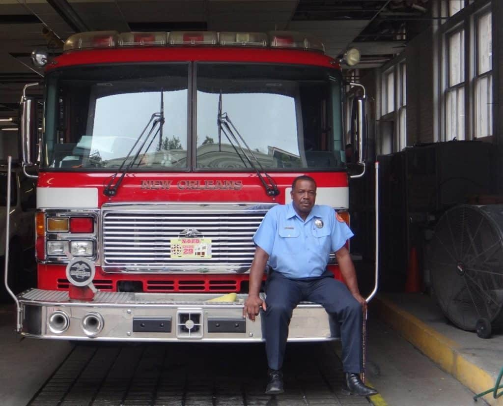 firefighter sitting on the front bumper of a fire engine