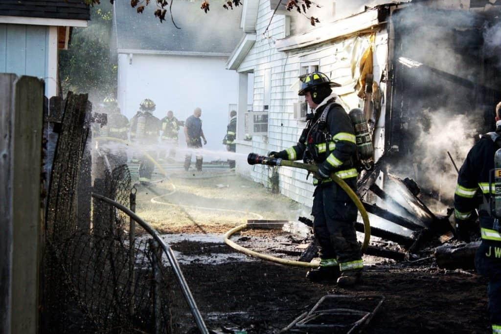 firefighter spraying burnt fence