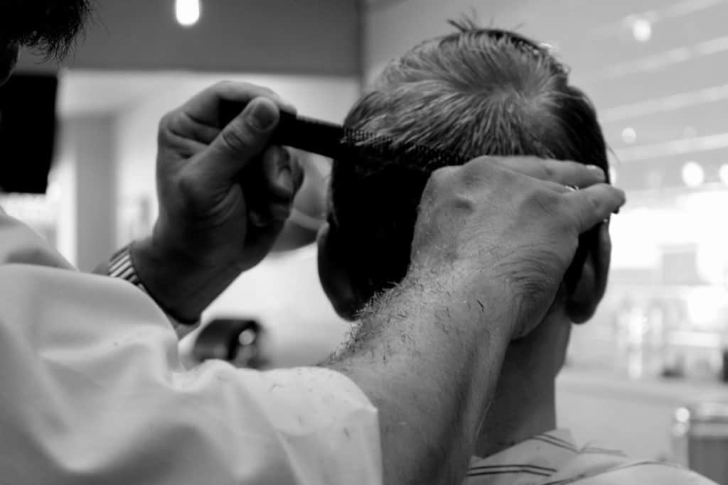 person getting haircut by barber