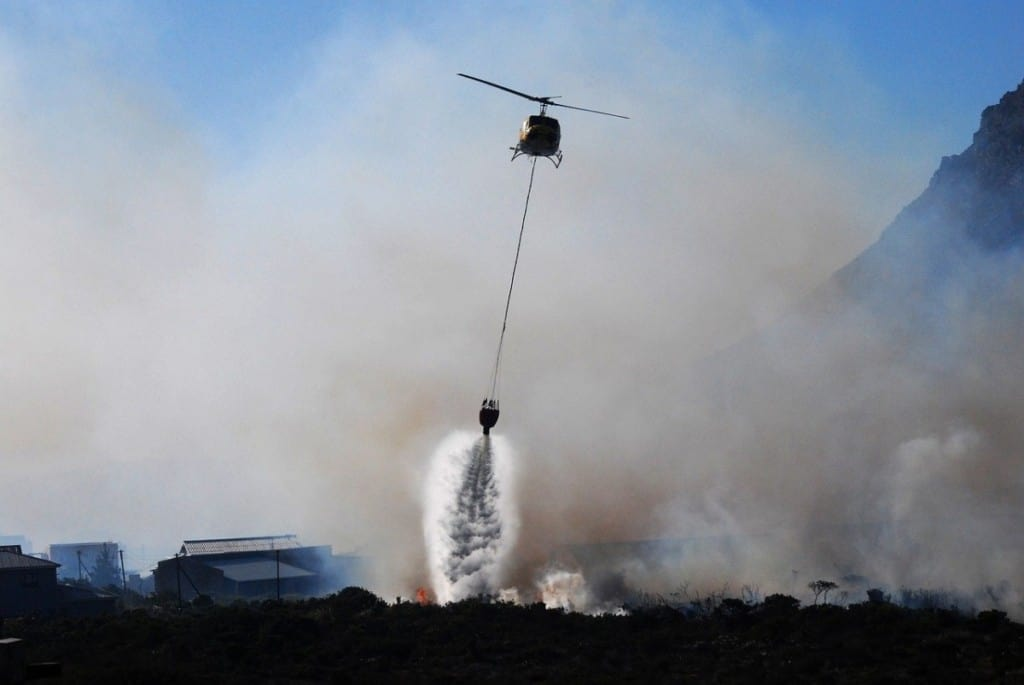 helicopter dropping water on smoky wildfire