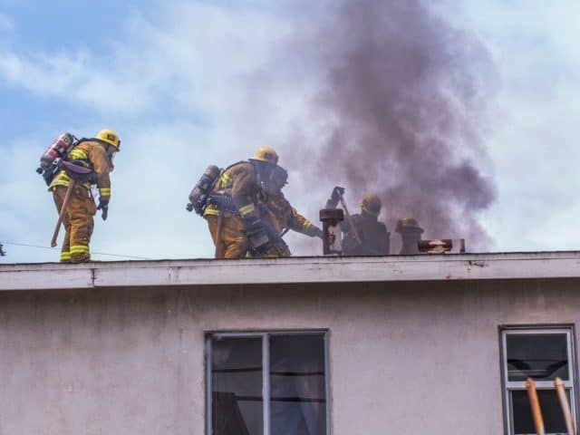 firefighters on roof cutting hole (vertical ventilation)